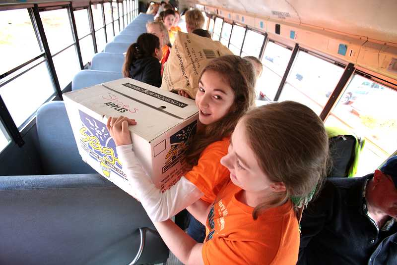 by: TIMES PHOTO: JONATHAN HOUSE - Mary Woodward Elementary School student Alyssa Anderson grabs a box of clothes during The Caring Closets annual Stuff the Bus clothing drive, on Friday.