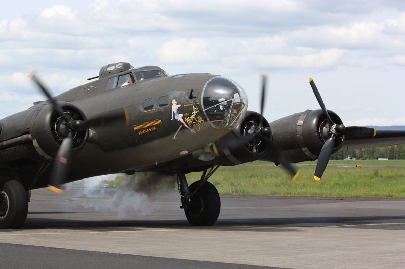 by: HILLSBORO TRIBUNE PHOTO: DOUG BURKHARDT - One of the four engines of the B-17 roars into life with a blast of smoke as the Memphis Belle prepapres for takeoff at the Hillsboro Airport.