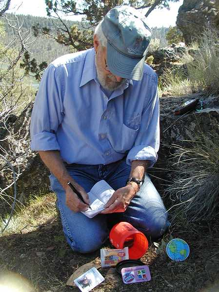 by: RON HALVORSON - Geocacher Lyle Andrews signs the log after retrieving a geocache from its hiding spot near Ochoco Reservoir.