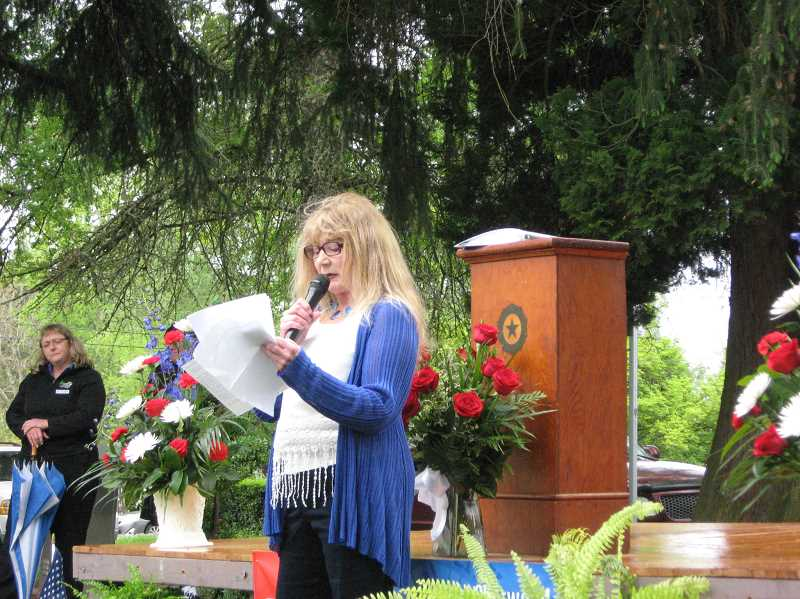 by: GAZETTE PHOTO: RAY PITZ - Tess Kies, a member of the Sherwood American Legion Auxiliary, reads about the attributes of former Sherwood Police Chief Delbert Stanislowski, who many around town simply referred to as 'Stan the Man,' during a dedication and tribute for the late chief.