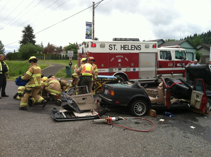 by: PHOTO COURTESY OF COLUMBIA RIVER FIRE & RESCUE - Emergency responders administer to Riley Holcomb, 22, a Columbia City man who was seriously injured in a collision between his BMW sedan and a tow truck on Highway 30 Saturday, May 3. Holcomb was ultimately evacuated to a hospital in Portland by helicopter for treatment.