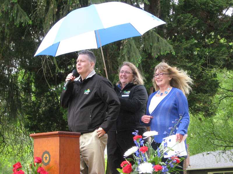 by: GAZETTE PHOTO: RAY PITZ - Sherwood City Manager Joe Gall addresses those attending a plaque installation for former police Chief Delbert Stanislowski May 3 as City Council President Linda Henderson and Tess Kies, who helped organize the memorial dedication, look on.