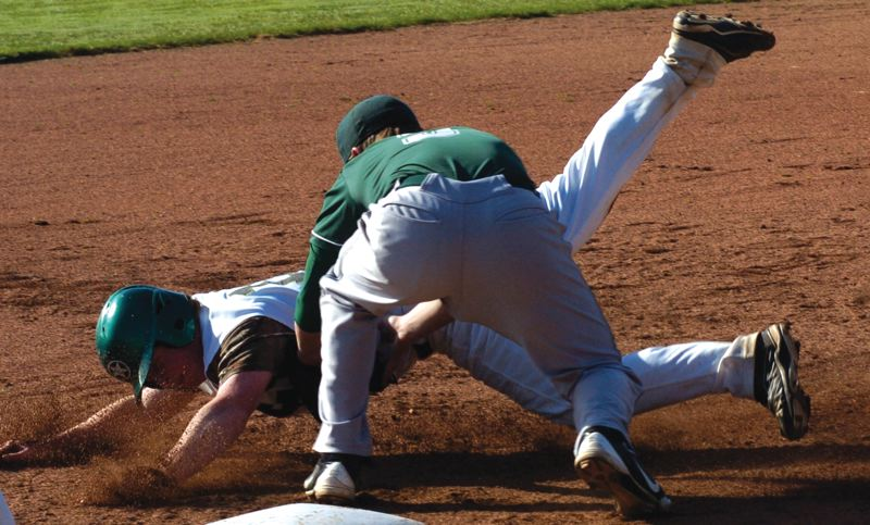 by: ESTACADA NEWS: PARKER LEE - Estacadas Casey Jones attempts to avoid the tag on a dive back to first base during last weeks home win over North Marion.