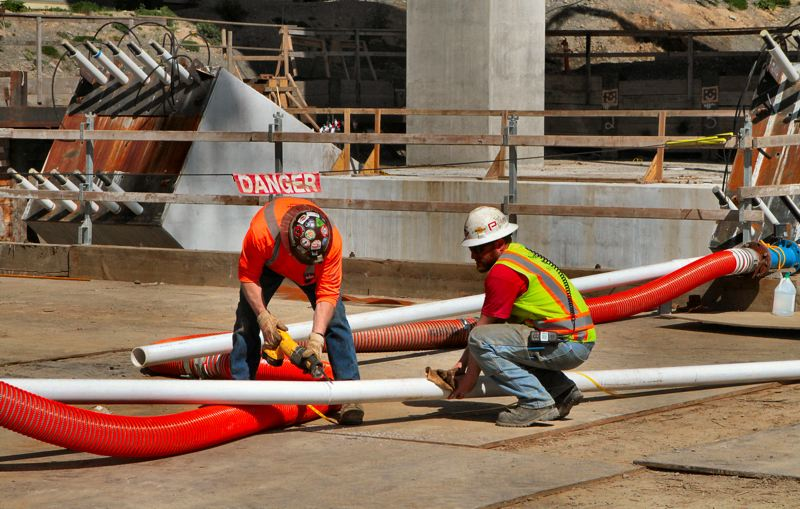 by: DAVID F. ASHTON - These plumbers are preparing the piping system that will circulate cooling water inside the concrete columns, while the Bent 6 cap beam high-strength concrete cures.