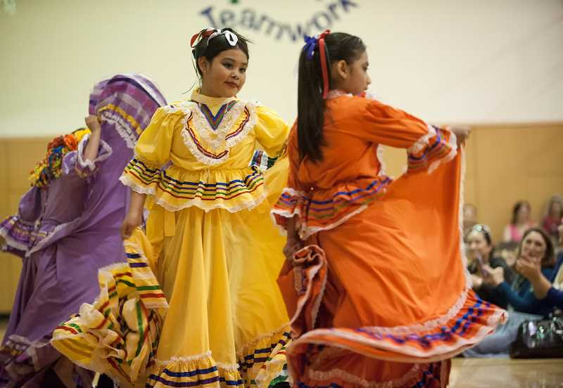 by: SPOKESMAN PHOTOS: JOSH KULLA - Ashley Garcia, center, dances for the students of Boeckman Creek Primary School with the Folklorico Group from Boones Ferry Primary.
