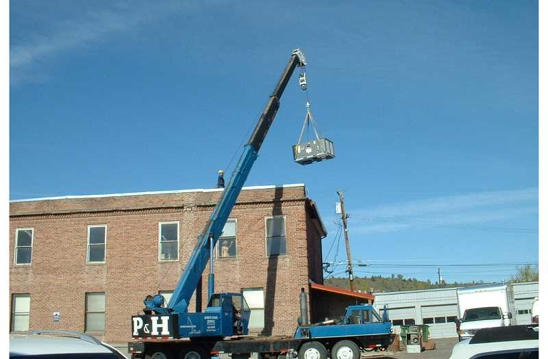 A crane lifts a new HVAC unit onto the top of the 'Origiinal Courthouse.'