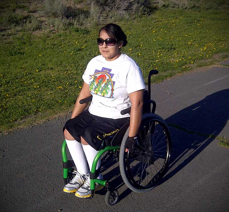 Selena Sahme practices on a track in her wheelchair.