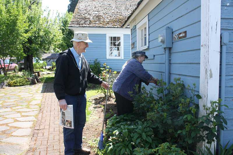by: PEGGY SAVAGE - Ret. Col. Jeff Knight and MAHS President Iris Riley work on last minute cleanup on the Dibble House museum complex grounds in preparation for the Quilt Show opening May 9.