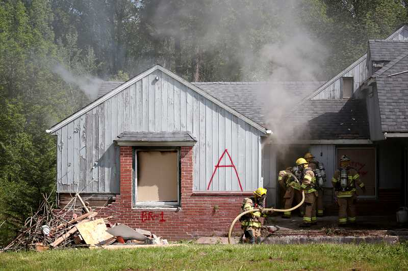 by: TIMES PHOTO: JONATHAN HOUSE - Tualatin Valley Fire & Rescue firefighter recruits snake a hose into an old house during a test burn Wednesday morning along Southwest Denney Road.
