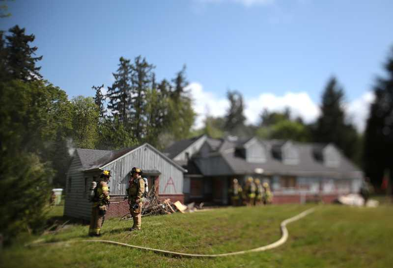 by: TIMES PHOTO: JONATHAN HOUSE - Tualatin Valley Fire & Rescue firefighter trainees and crews practice a test burn on an old house on Southwest Denney Road.