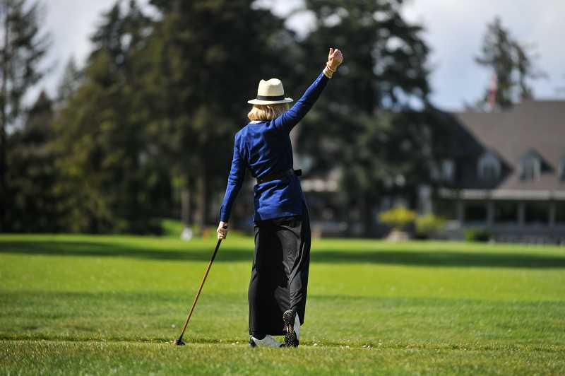 by: TIMES PHOTO: JOHN LARIVIERE - Diane Fraser raises her arm as she celebrates a solid tee shot down the middle of the fairway on the ninth hole during the two-hole scramble, where members dressed in period clothing and used hickory shaft clubs.