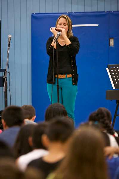 by: TIMES PHOTO: JAIME VALDEZ - Susan Sauter plays a classical song on a harmonica for first- and second-grade students at Vose Elementary School.