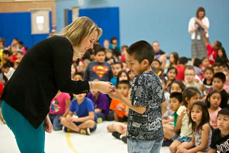 by: TIMES PHOTO: JAIME VALDEZ - Susan Sauter presents a miniature harmonica to first-grader Tony Padilla at Vose Elementary School.