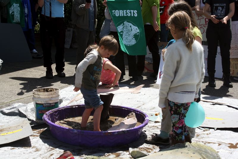 by: POST PHOTO: KYLIE WRAY - Children hold their signs in the mud, symbolizing harm to salmon.