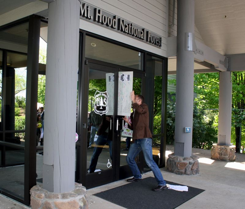 by: POST PHOTO: KYLIE WRAY - Bark Executive Director Alex Brown delivers a giant letter to Lisa Northrop through the locked doors of the Forest Service office.