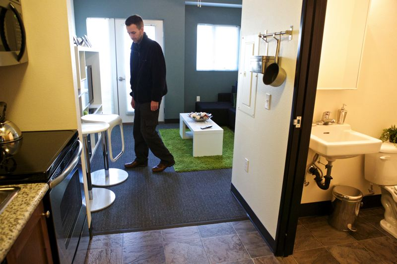 by: TRIBUNE PHOTO: JAIME VALDEZ - Freedom Center business manager shows off a 279-square-foot apartment at the Freedom Center that includes a bathroom and kitchen. Some building residents eat their meals in the communal lounge, and many stay a year or less, temporarily sacrificing space for location.