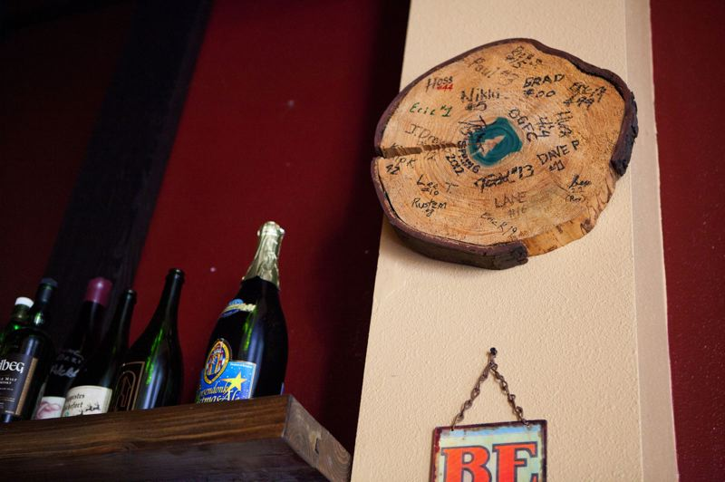by: TRIBUNE PHOTO: ADAM WICKHAM  - A signed Portland Timbers log slab hangs and other soccer paraphernalia adorn the walls of Bazi Bierbrasserie. Venture Portland is helping neighborhood business districts invest in their soccer-loving communities.
