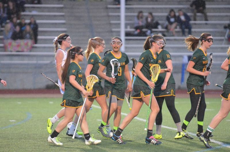 by: JEFF GOODMAN - West Linn's girls lacrosse team celebrates a goal following the Lions' recent victory against Wilsonville. West Linn has one regular season game remaining.
