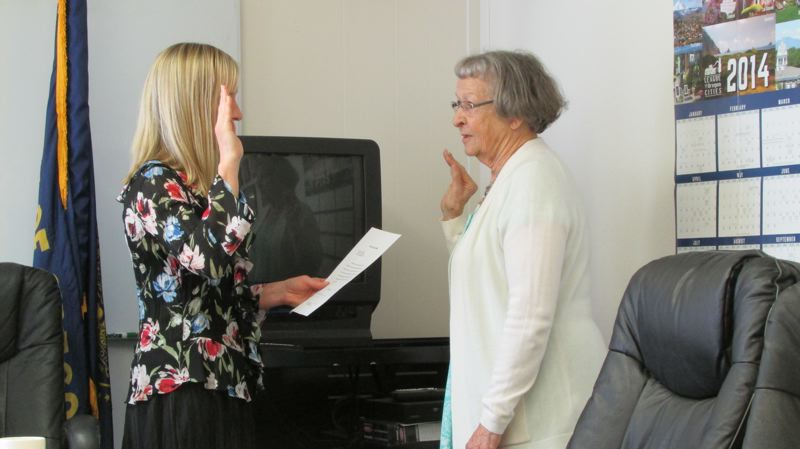 by: MARK MILLER - Nell Harrison (right) takes the oath of office to become a member of the City Council of Columbia City Thursday, May 1. Administering the oath is Leahnette Rivers (left), city administrator and recorder.