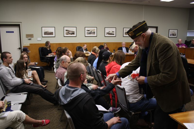 by: SPOTLIGHT PHOTO: ROBIN JOHNSON - John Vinson, army veteran with Scappoose Veterans of Foreign Wars Post 4362, passes out Buddy Poppies to the audience of Mondays Scappoose City Council meeting.