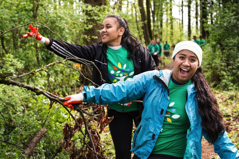 by: CONTRIBUTED PHOTO: COURTNEY ZEREZIF - Kaila Killion (left) and Nelyn Phillip work together to pull out fallen branches blocking the pathway in Columbia Park on Comcast Cares Day.