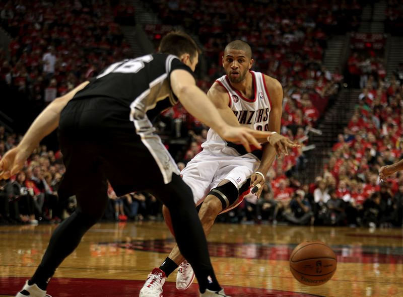 by: TRIBUNE PHOTO: JONATHAN HOUSE - Nicolas Batum tries to bounce a pass through the San Antonio defense.