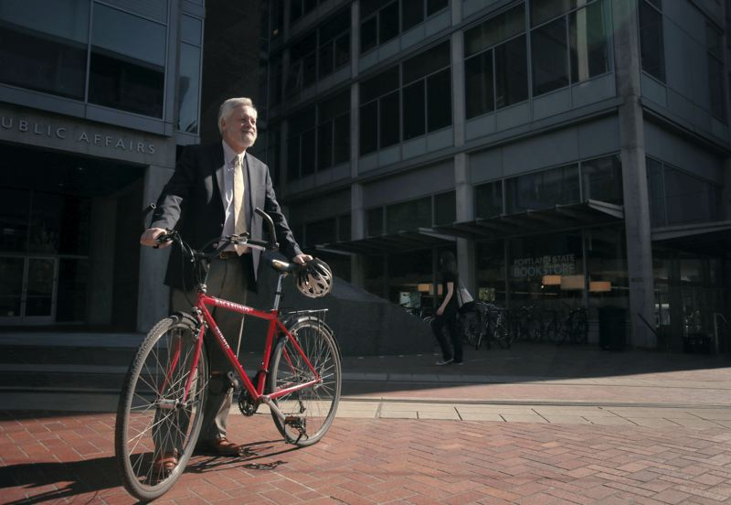 by: PAMPLIN MEDIA GROUP: JONATHAN HOUSE - Robert Liberty with a bike at the Urban Plaza at Portland State University.