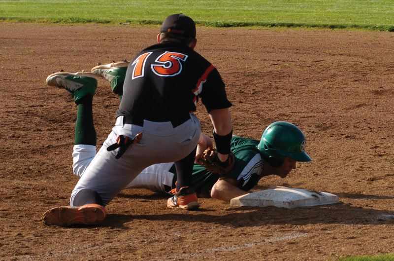 by: ESTACADA NEWS: PARKER LEE - Estacadas Zach Stamm dives safely back to first base on a pick-off attempt against Gladstone.