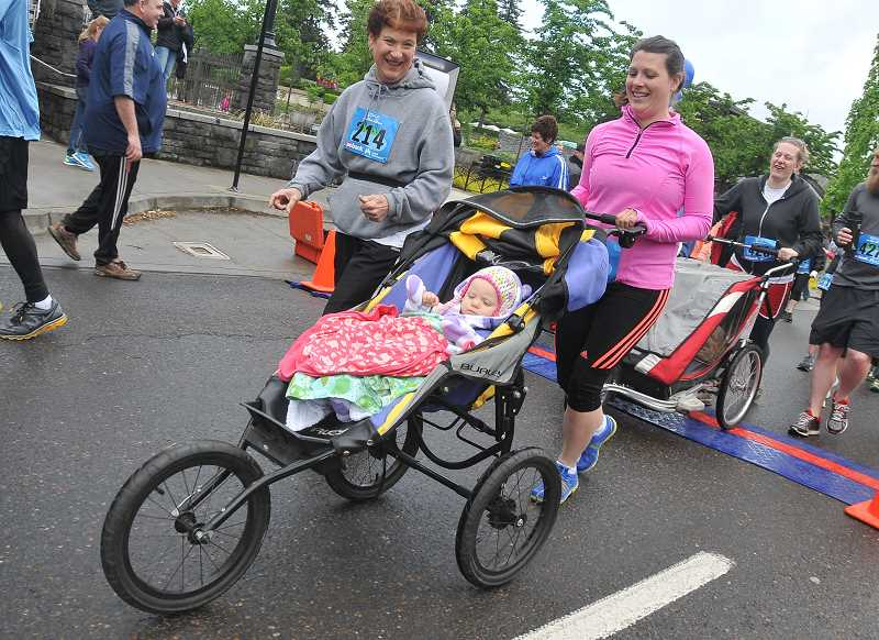 Eleanor Conway goes along for the ride as her mother, Heidi Conway, pushes the cart in the 5 k race.