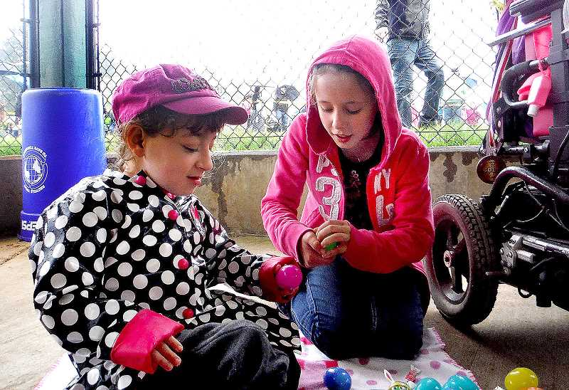 by: CONTRIBUTED - Bryten Figgins and Hannah Crandell go over the spoils from the annual Estacada Fire Department Easter Egg Hunt on Saturday, April 19.