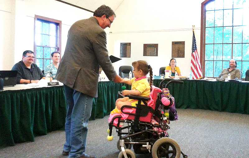 by: ISABEL GAUTSCHI - Mayor Brent Dodrill gives Bryten a copy of the proclamation declaring May 6 as Community Osteogenesis Imperfecta (OI) Awareness Day in Estacada during the city council meeting on Monday, April 28.