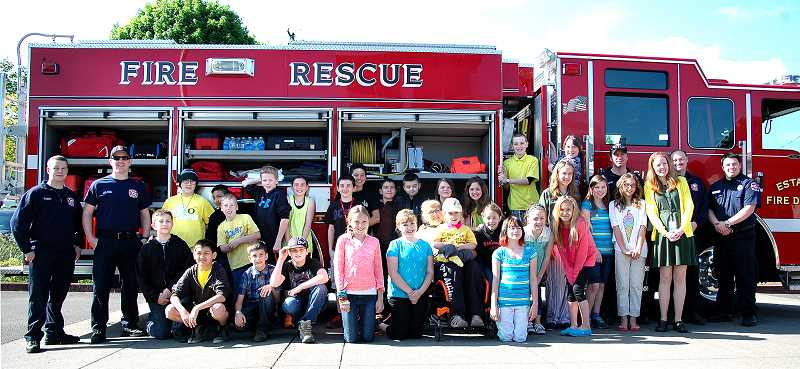 by:  ISABEL GAUTSCHI - Bryten and Teryl Figgins (center) pose with Amy Munds' fifth-grade class and members of the Estacada Fire Department for OI Awareness Week on Wednesday, May 7.