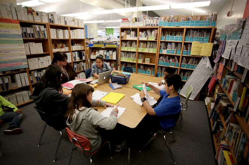 by: TIMES PHOTO: JONATHAN HOUSE - ESL teacher Deborah Harpine leads her reading group in a corner of Vose Elementary's library. They put up book shelves as walls to create a temporary room to make the instruction a little more private.