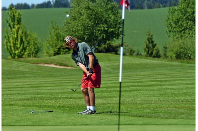 by: DAN BROOD - SURE SHOT -- Tigard senior Damien Vonahelfeld chips onto the green on hole No. 15 during play Tuesday at the Pacific Conference boys golf district tournament, held at Quail Valley.