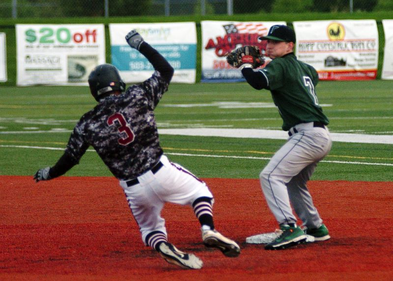 by: DAN BROOD - MAKING THE PIVOT -- Tigard senior second baseman Bruin Campbell (right) looks to make a throw to first after forcing out Tualatin's Tanner Marsh.