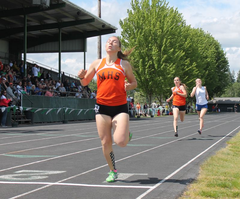 by: JIM BESEDA/MOLALLA PIONEER - Molalla's Emily Bever wins the 800-meter run for the fourth consecutive season while younger sister Audrey Bever overtakes La Salle's Kate Christoferson for second place at Saturday's Tri-Valley Conference track and field district championships at North Marion High School.
