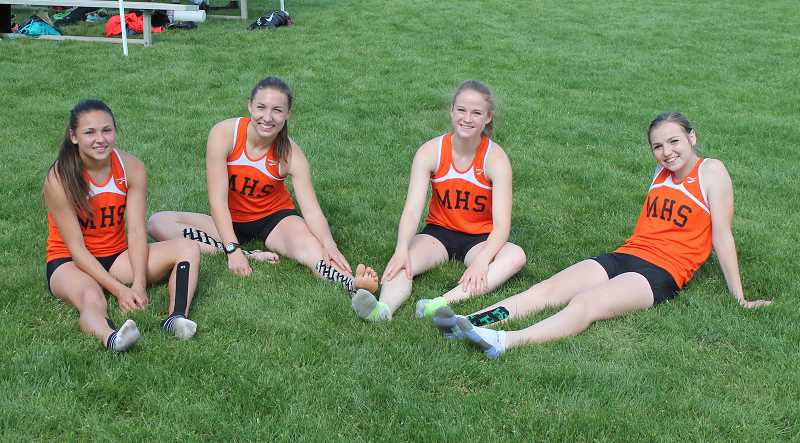 by: JIM BESEDA, MOLALLA PIONEER - Molalla's girls' 4x400 meter relay team of Desiirae DesRosiers, Emily Bever, Josie Child and Audrey Bever relax Saturday after posting a winning time of 4:14.44 in qualifying for next week's Class 4A track and field state championships in Eugene.