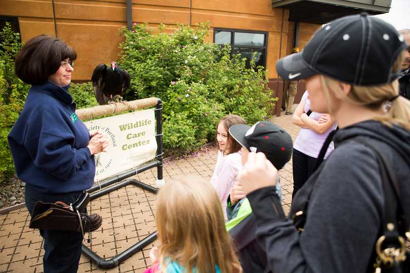 by: TIMES PHOTO: DAVID BLAIR - Cecile Valastro, an Audubon Society of Portland volunteer, instructs visitors about a vulture on display during the Tualatin River Bird Festival.