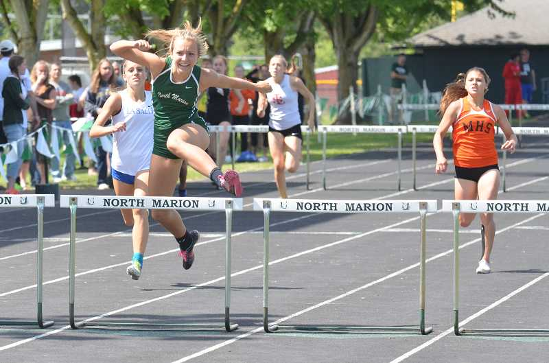 by: JEFF GOODMAN / PAMPLIN MEDIA GROUP - North Marion senior Hannah Waite clears the final hurdle of the girls 300-meter hurdles race May 17 at North Marion High School, where she won Tri-Valley Conference track and field district titles in both hurdles races.