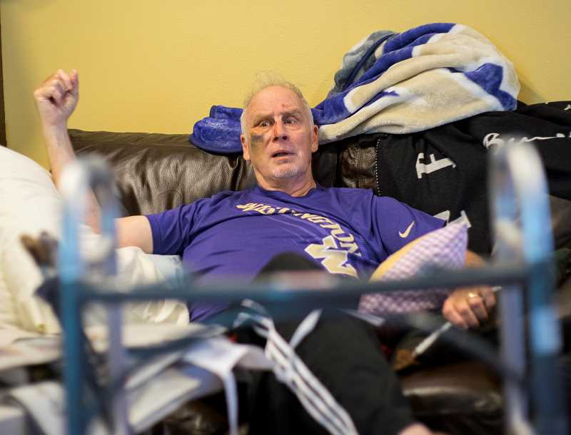 by: NEWS-TIMES PHOTO: CHASE ALLGOOD - Forest Grove Mayor Pete Truax talks about his May 7 motor-scooter accident and its aftermath from a couch in his Forest Gale Heights living room. A Pacific University alum but a fan of the University of Washington, Truax wears the signature Husky colors of purple and gold as he rests up.