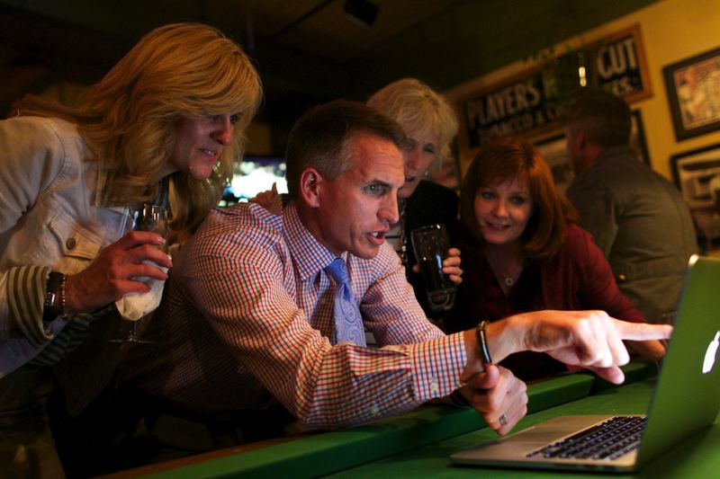 by: TIMES PHOTO: JAIME VALDEZ - Flanked by Beaverton School District board members and staff, Superintendent Jeff Rose zeroes in on Tuesday night's election results for the district's $680 million bond measure from a private room at McMenamins Cedar Hills Pub.