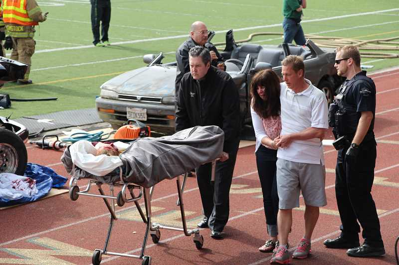 by: SUBMITTED PHOTO: BRITTANY PARK - Ashley Johnson is the last victim removed from the simulated accident scene.  Her parents, Marijean and Brett, accompany her on the short ride to the morticians car.