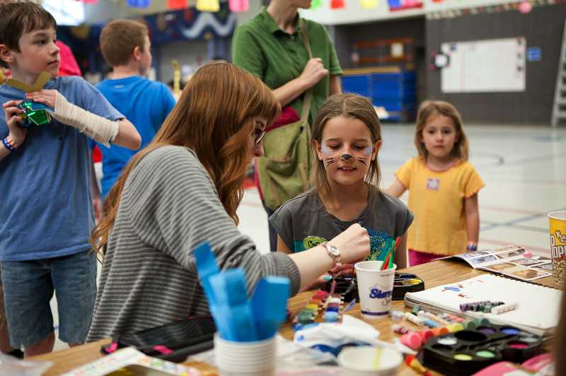 by: TIMES PHOTO: ADAM WICKHAM - Masha Khartikova, 9, gets her face painted.