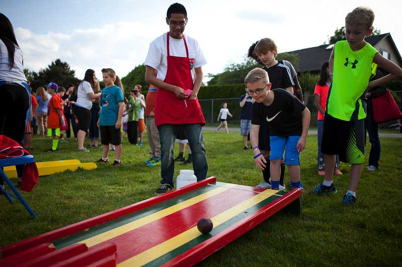 by: TIMES PHOTO: ADAM WICKHAM - Parker Arbuthnot, 11, plays a skee-ball game while his friend Anders Turman, 11, (right) and Aloha High School student and volunteer Brian Vasquez watch.