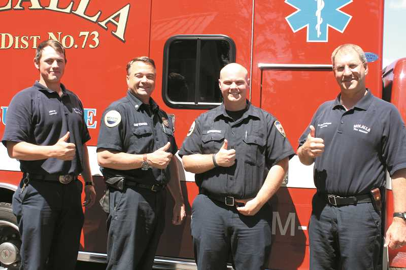 by: PEGGY SAVAGE - From left: Molalla Fire District firefighter/paramedic Dallas Oja, Chief Vince Stafford, firefighter/paramedic Estabrook and Lt. Mike Berrington give a thumbs up Wednesday after voters passed both a levy and bond measure to support the district.