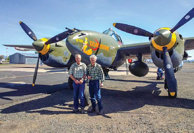 by: JANET BROWN - Rex Barber Jr., of Terrebonne, and Jack Erickson, pose with Erickson's P-38 Lightning, which is similar to the one flown by Barber's father during World War II.