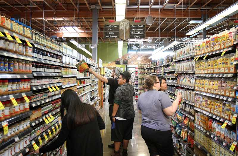TIMES PHOTO: JONATHAN HOUSE - Whole Foods employees prepare the shelves for the stores new location in Tigard.