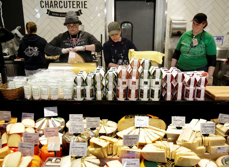 TIMES PHOTO: JONATHAN HOUSE - Whole Foods employees prepare the cheese department at the stores new location in Tigard.