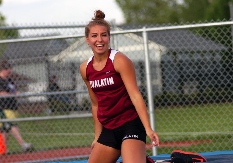 by: DAN BROOD - Tualatin High School senior Laura Taylor smiles after clearing 12 feet in the pole vault competition at last week's Pacific Conference district track and field championships.