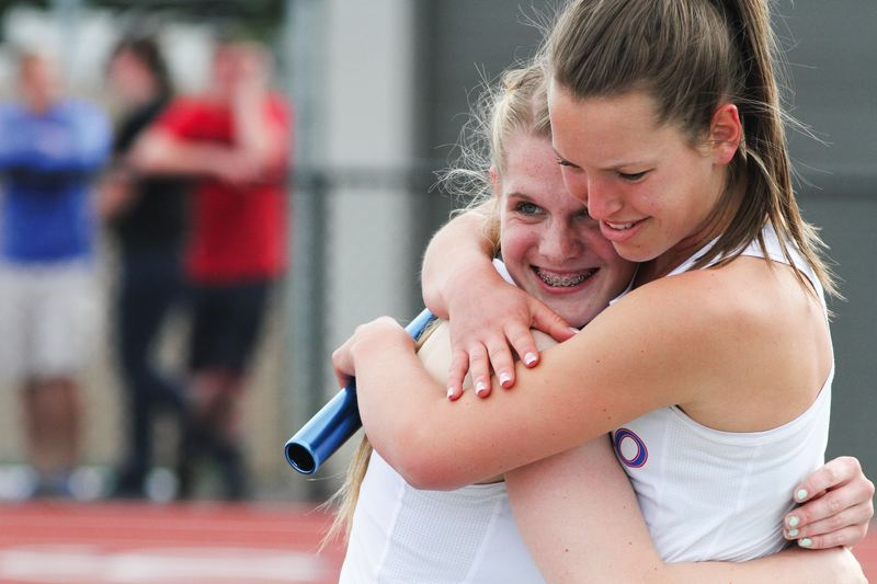 by: HILLSBORO TRIBUNE PHOTO: AMANDA MILES - Hillsboro teammates Kylee Taube (right) and Anna Dean share an embrace after helping the Spartans to victory in the 4x100-meter relay last Friday at the district track meet.
